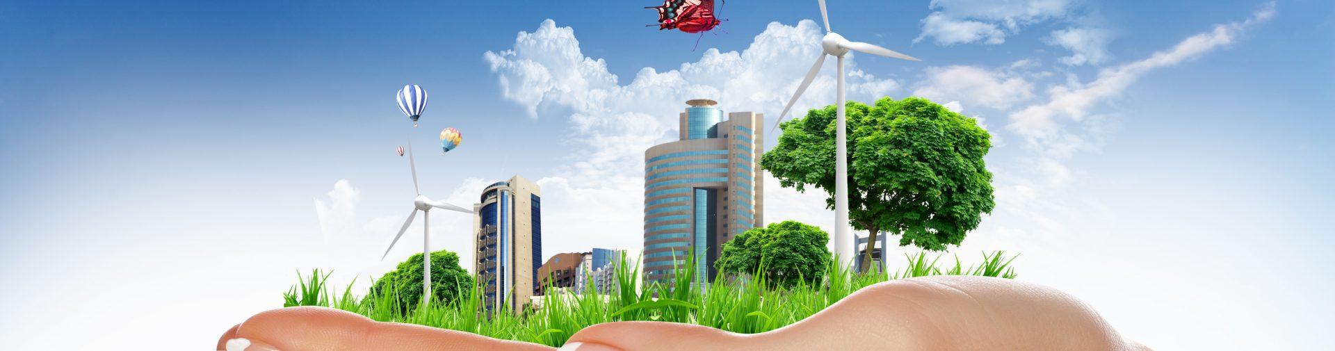 Human hand holding a city on green grass hill